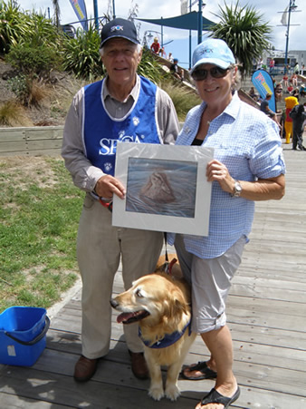 "SPCA volunteers with a donated giclee print of ""Lil Swimmer"" by Artist Karen Neal"